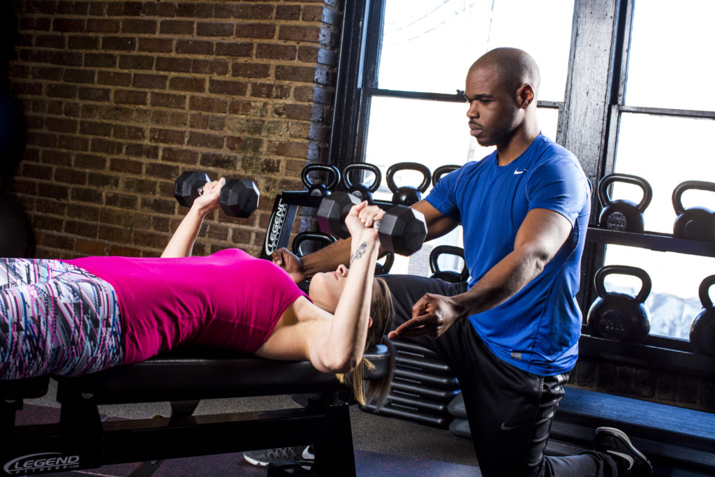 Personal Trainer working with a client. He is coaching her form while she performs a dumbbell bench press.